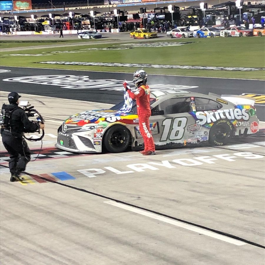 Kyle Busch poses in front of his Skittles Zombie car after winning the Autotrader EchoPark 500